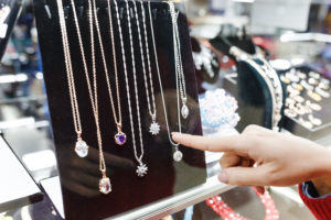 Woman's hand pointing at jewelry in glass display case