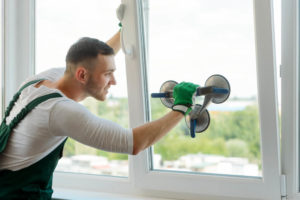 Man repairing window using vacuum lifte