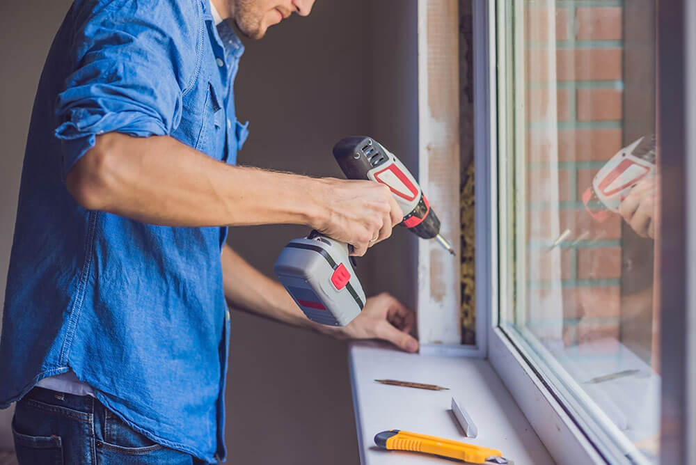 Man in blue shirt does window installation