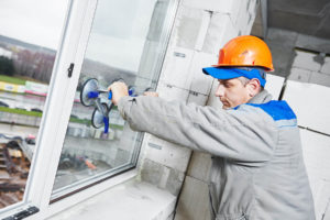 Male industrial worker at window installation construction site