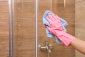 Housewife washing and polishing a glass shower door