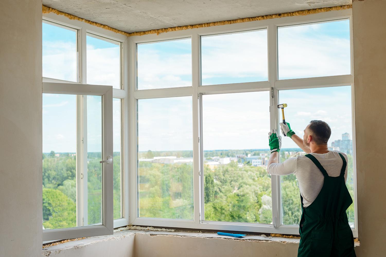 Worker is installing a corner window