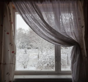 Winter window scene with white drapes and snow outside
